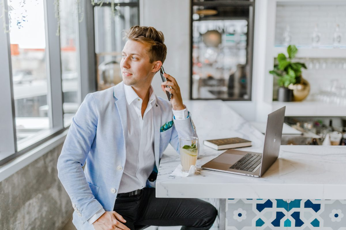 man working remote from home talking on his cell phone